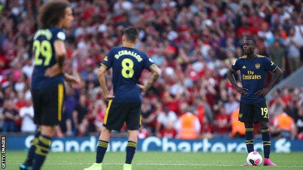 Arsenal players look disconsolate after conceding a third goal against Liverpool