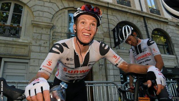 Soren Kragh Andersen smiles as he leans on his bike after winning stage 14 of the 2020 Tour de France
