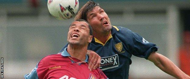 Mick Harford (right) contests a header