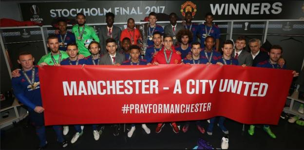 The Manchester United players pose with a banner for those who lost their lives in the Manchester attack