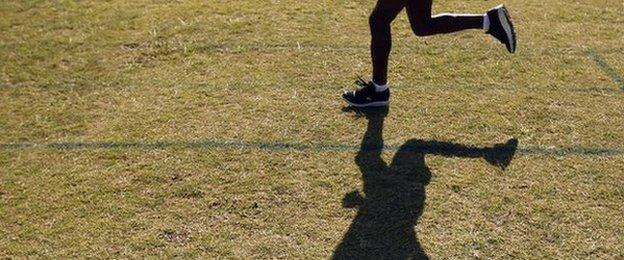 A runner trains on the grass and is shadowed by the sun