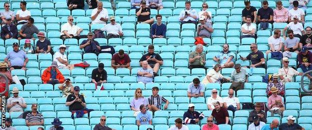 Fans sit socially distanced