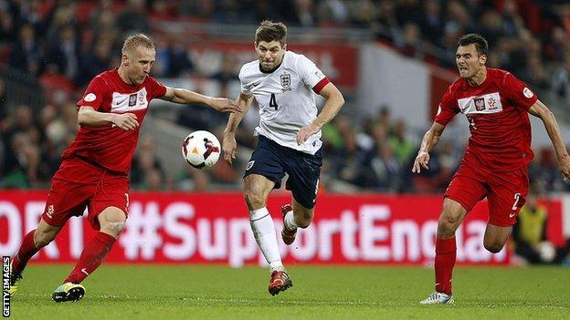England's Steven Gerrard takes on two Poland players in 2013