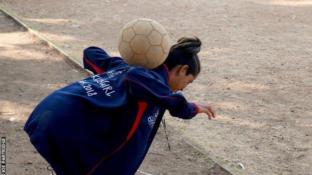 Saini juggles a football on her back