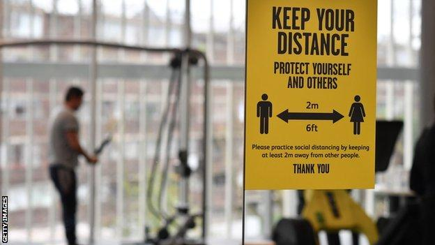 A sign reminds gym users of social distancing protocols as they exercise on the machines at Kensington Leisure Centre in London