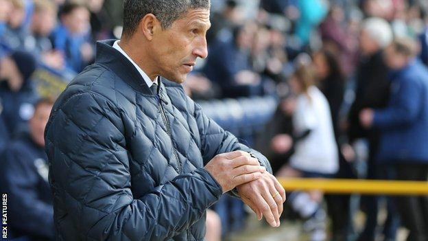 Brighton boss Chris Hughton checks his watch at Deepdale