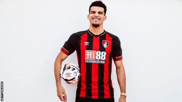 Striker Dominic Solanke smiles while holding a football and wearing a Bournemouth shirt following his move from Liverpool