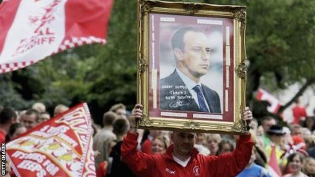 A Liverpool fan holds up a picture of Benitez during the bus parade after the 2005 Champions League final