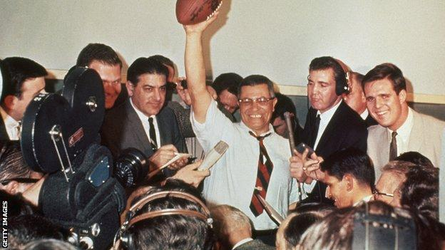 Green Bay Packers coach Vince Lombardi raises a football in victory, surrounded by reporters covering the first Super Bowl in 1967.