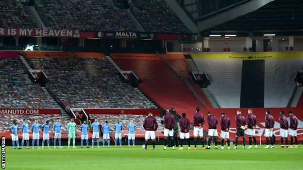 Manchester United and Manchester City player's observing a minute's silence for Colin Bell