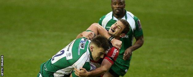 Johnny Williams of London Irish fends off a tackle by Francois Bouvier of Agen