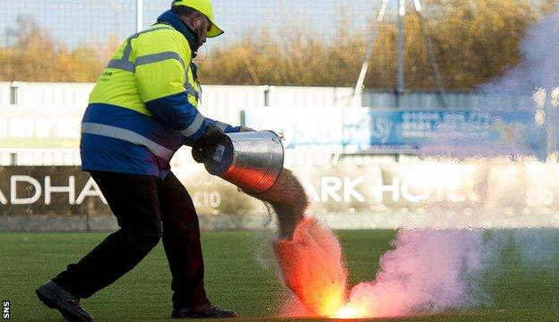 A steward puts out a flare thrown on to Falkirk's artificial pitch