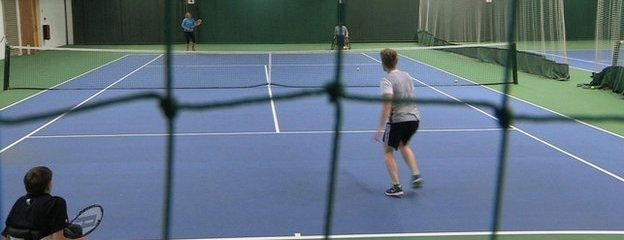 Able-bodied and wheelchair doubles much in an indoor tennis court