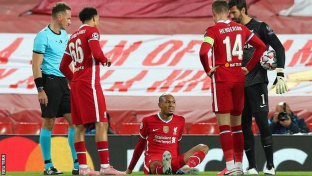 Liverpool defender Fabinho sits on the pitch after sustaining an injury during the Champions League group game with Midtjylland