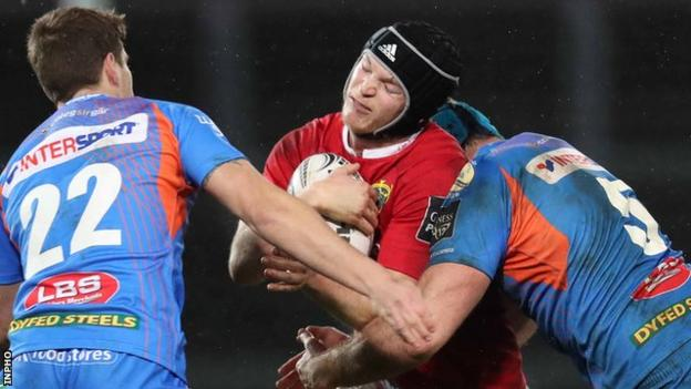 Munster's Tyler Bleyendaal is halted by a tackle from Scarlets replacement Aled Thomas