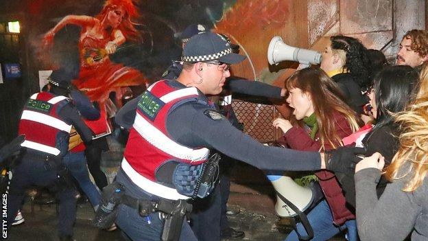 Police officers attempt to stop protesters from storming the back entrance to Melbourne's Athenaeum club, where Court was the keynote speaker on 22 June 2017