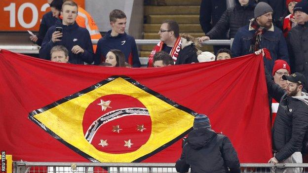 Liverpool fans carry a flag with Chapecoense team named on it