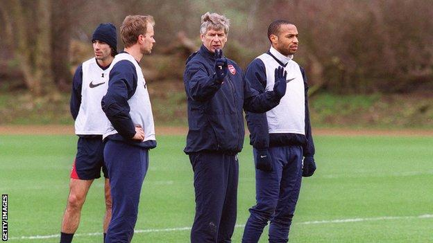 Arsene Wenger chats to Thierry Henry and Dennis Bergkamp during an Arsenal training session on March 23 2004