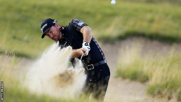 Graeme McDowell plays out of a bunker at the 16th in the first round