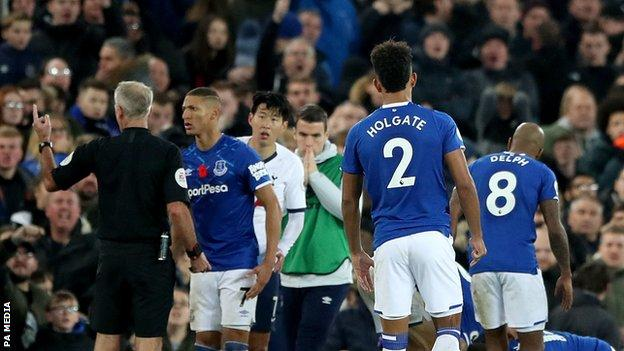 Everton players console Andre Gomes after suffering a serious ankle injury against Tottenham