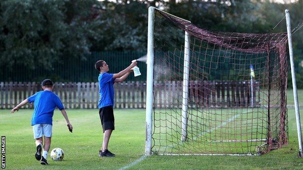 Children sanitise goalposts at Aylesbury Vale Dynamos FC
