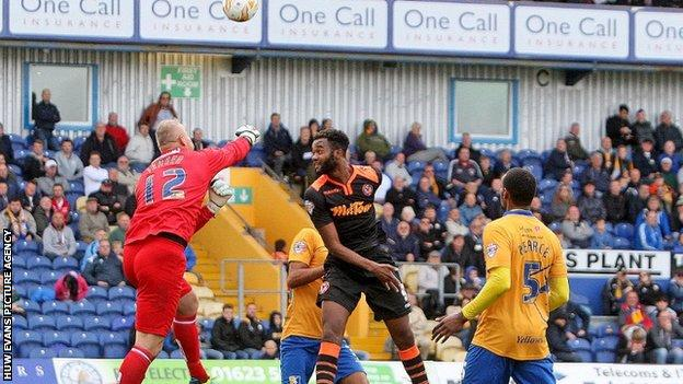 Brian Jensen of Mansfield clears the danger from Zak Ansa