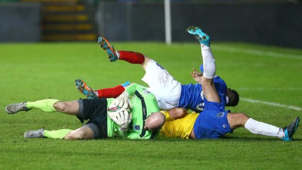Linfield striker Paul Smyth lands on top of Ballymena United keeper Alan Blayney and defender Johnny Taylor