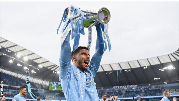 Ruben Dias holds aloft the Premier League trophy
