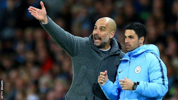 Manchester City manager Pep Guardiola points as he talks to assistant Mikel Arteta (right)