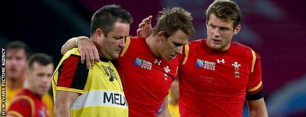 Liam Williams is helped off the field by Dr Geoff Davies
