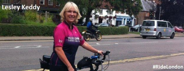 Lesley Keddy on a road, holding her bike
