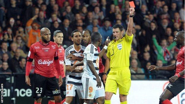 Majeed Waris (centre) is shown the red card by the referee