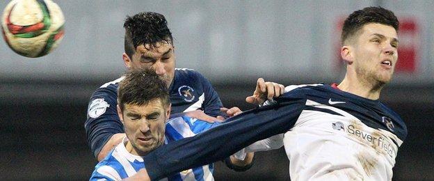 Coleraine's Steven Douglas goes for a high ball against Emmett Friars and Adam Leckey of Ballinamallard