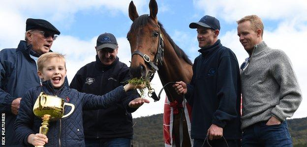 2016 Melbourne Cup Winner Almandin with (left to right) owner Lloyd Williams, trainer Rob Hickmott, Joel Flannery and Australian Jockey Kerrin Mcevoy with Lloyd's grandson Frank Williams holding the Melbourne Cup