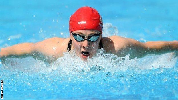 Close up photograph of Siobhan-Marie O'Connor, wearing a red swimming cap and goggles, swimming towards the camera.