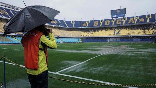 Photographer takes picture of waterlogged pitch at Boca's La Bombonera stadium.
