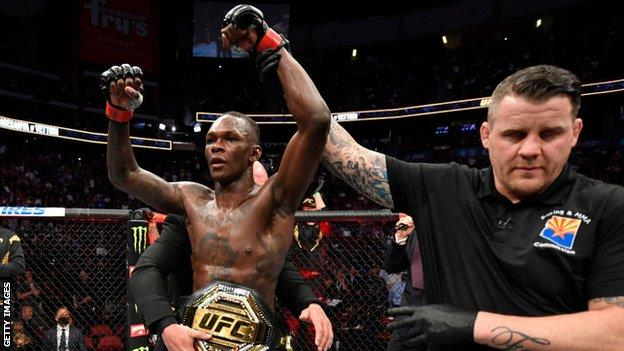 Israel Adesanya celebrates retaining his middleweight title at UFC 263