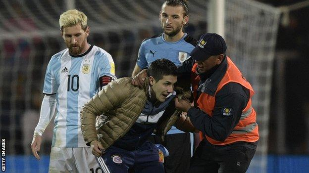 But then gets bundled off the pitch by a security guard