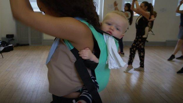 A mother with a baby in a sling during a dance class