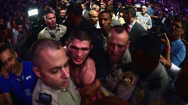 Khabib Nurmagomedov being taken away from the octagon by police