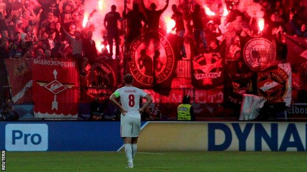 "Spartak Moscow""s Denis Glushakov as fans set off flares in the stands"
