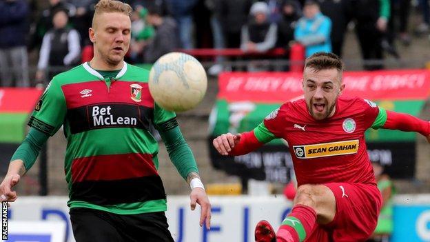 Glentoran's Deivydas Matulevicius closes in as Cliftonville midfielder Conor McMenamin unleashes a shot