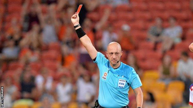 Referee brandishing a red card