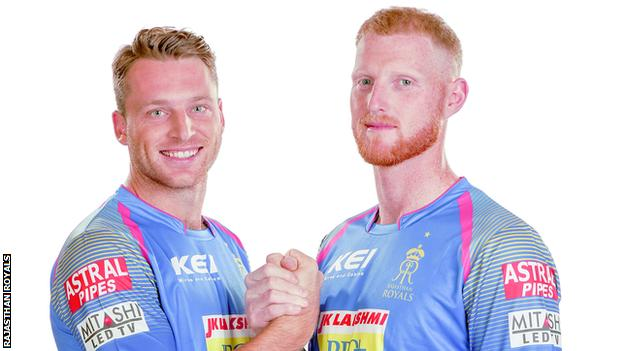 England cricketers Jos Buttler (left) and Ben Stokes (right) clasp hands while wearing their Rajasthan Royals kit