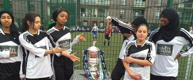 A girls football team pose by the Women's FA Cup
