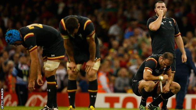 Wales players slumped in relief and fatigue after the final whistle against Fiji