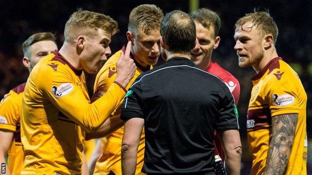 Motherwell players protest referee Willie Collum's decision to award Celtic a late penalty