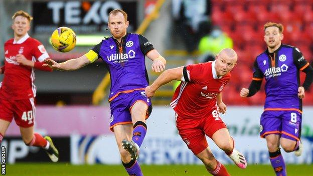 Mark Reynolds of Dundee United challenges Curtis Main of Aberdeen