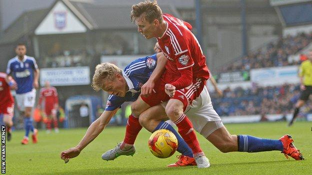 Joe Mason of Cardiff is fouled by Jonathan Parr of Ipswich