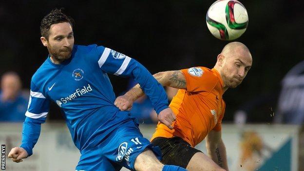Ballinamallard's Jay McCartney and Carrick midfielder Barry Johnston tussle for the ball